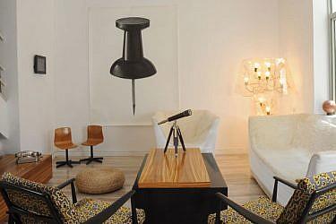 """רישום ענק של אירינה בירגר, המגדילה לממדי ענק חפצים יומיומיים קטנים, נתלה על קיר מרכזי בסלון. על הקיר הניצב נתלתה עבודת וידיאו של צמד אמני המיצג """" בית הזכוכית"""". צילום: סוזי לוינזון"""