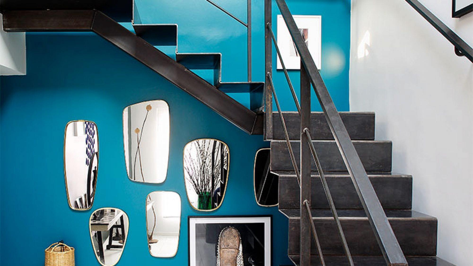 בכניסה המרשימה לבית שולבו מגוון אלמנטים הלוכדים את תשומת הלב של הבאים, בהם מדרגות מתכת, קיר בגון טורקיז ואוסף מראות וינטג' | צילום: Francis Amiand