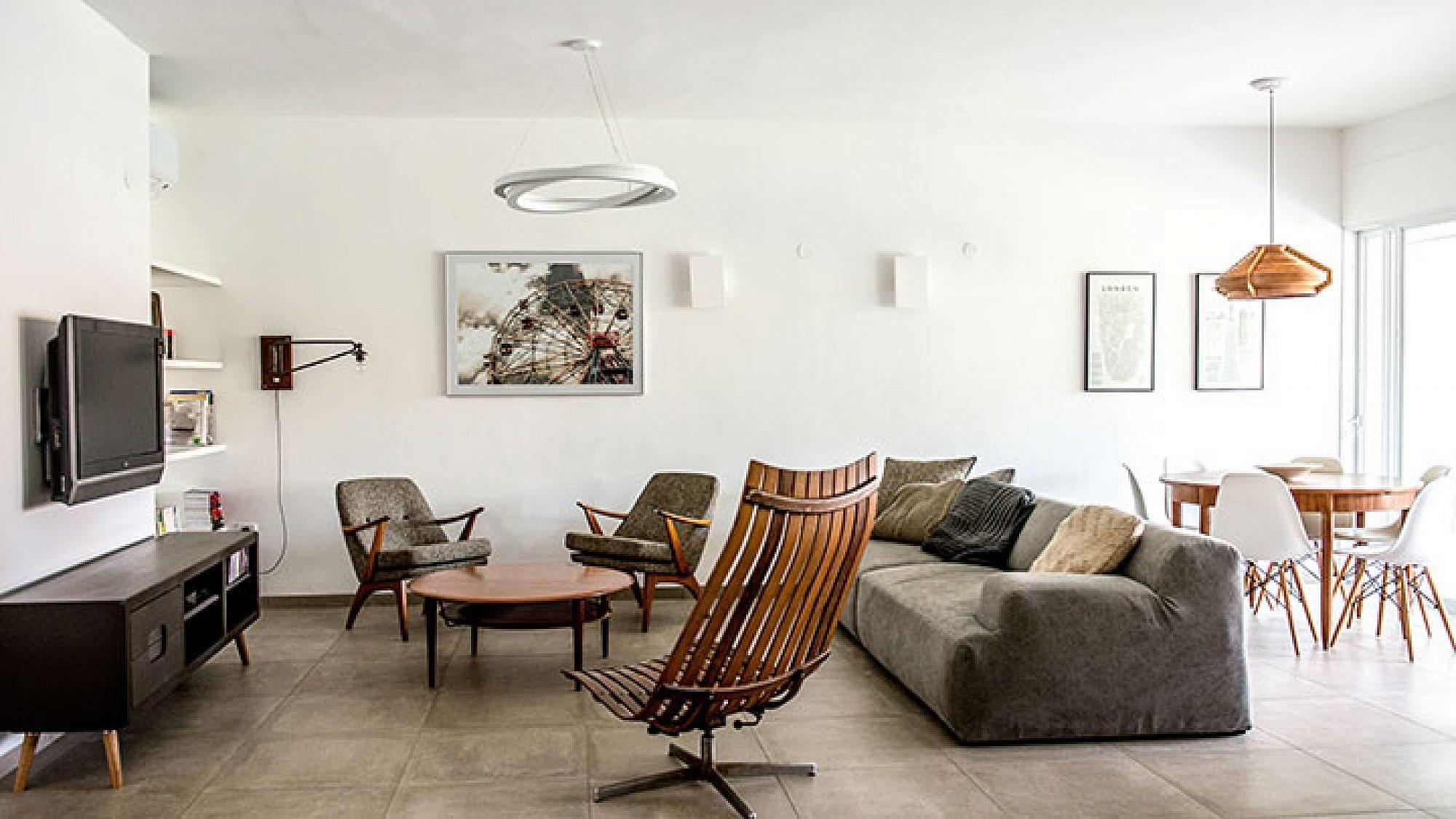 פסיפס אקלקטי של רהיטים ופריטי עיצוב בגוונים מונוכרומטיים יוצרים חלל ציבורי נעים ומתוחכם הכולל את הסלון ואת פינת האוכל | צילום: סיון אסקיו