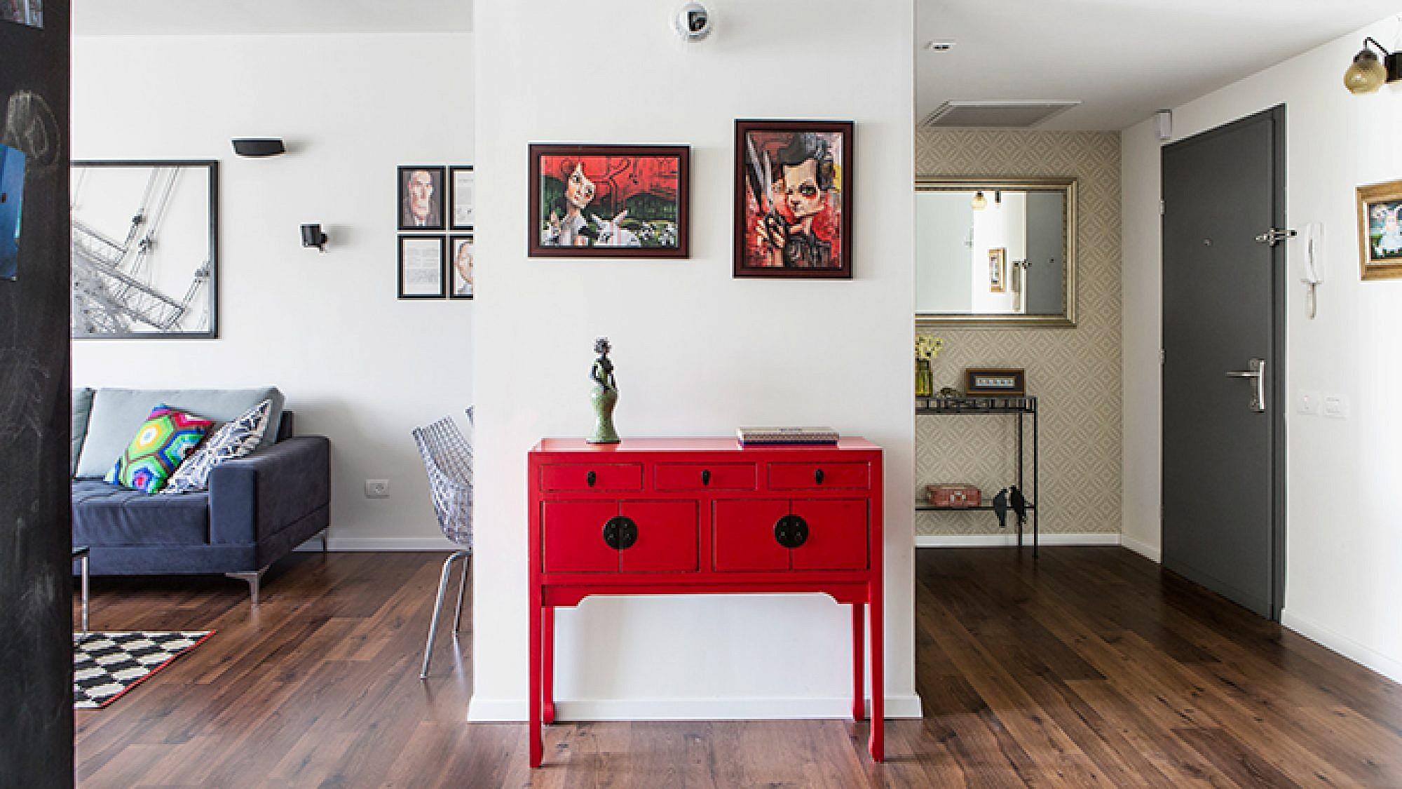 מבט לעבר הסלון והכניסה. השידה האדומה נרכשה בשוק הפשפשים. מאחורי השידה מימין ארון אחסון גדול, משמאל פינת העבודה | צילום: איתי בנית