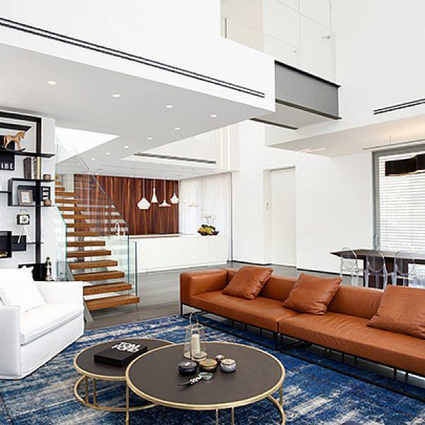 מוטיב העיגול בכיסאות, בגוף התאורה ובשולחנות הסלון שובר את הנוקשות והמרובעות של החללים בבית במושב אירוס | צילום: אורי אקרמן
