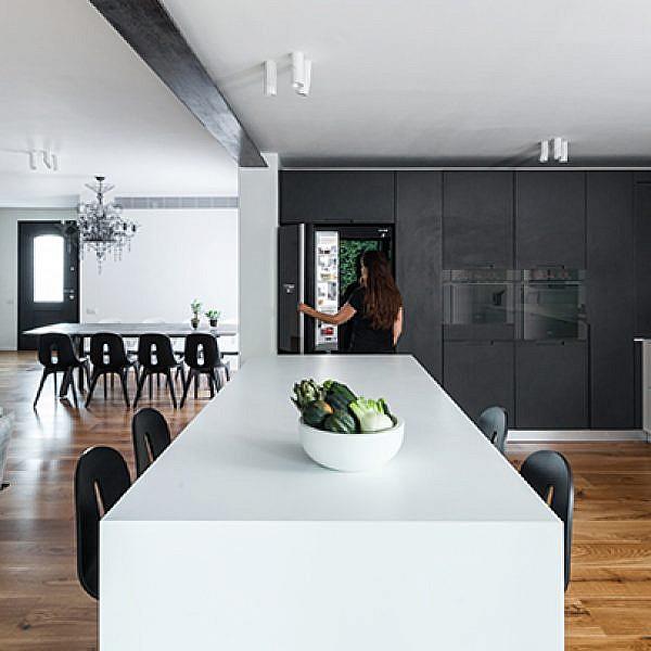 פלטת הצבעים שנעה בין לבן לשחור עם גוני ביניים אפורים ופרקט עץ אלון יוצרת נראות מודרנית אך חמימה וביתית | צילום: טל ניסים