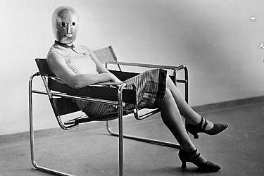 אריך קונסמולר, אשה יושבת על כיסא וסילי בעיצוב מרסל ברוייר, ועל פניה מסכה של אוסקר שלמר, 1926 בקירוב, תצלום שחור-לבן | ארכיון באוהאוס, ברלין