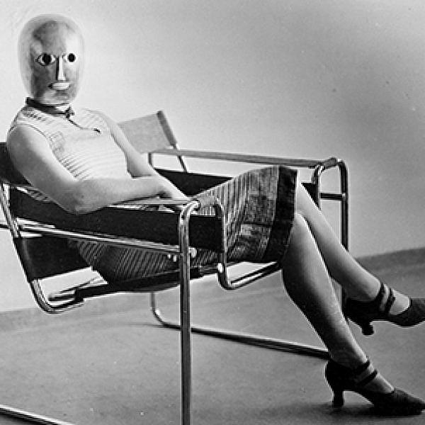 אריך קונסמולר, אשה יושבת על כיסא וסילי בעיצוב מרסל ברוייר, ועל פניה מסכה של אוסקר שלמר, 1926 בקירוב | ארכיון באוהאוס, ברלין