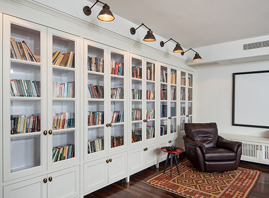 חמישה גופי תאורה מפליז בסגנון תעשייתי-קלאסי, הותקנו במדויק מעל דלתות ספריית הקיר המשפחתית. הלומת האור הרכה מאפשרת קריאה באור פרקטי ונעים   עיצוב פנים: סמדר אביגדורוב   צילום: אביב קורט