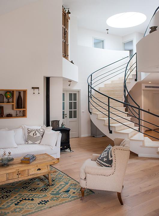 """סקיילייט עגול בתקרה מכניס אור יום פנימה ומאיר את גרם המדרגות ואילו ספוטים מפזרים את האור בצורת הלומות למעלה ולמטה על הקיר, כך שאזורים דומיננטיים יהיו מוארים יותר וחלקים """"מתים"""" יהיו פחות מוארים   עיצוב פנים: דנה שבדרון   צילום: גלעד רדט"""
