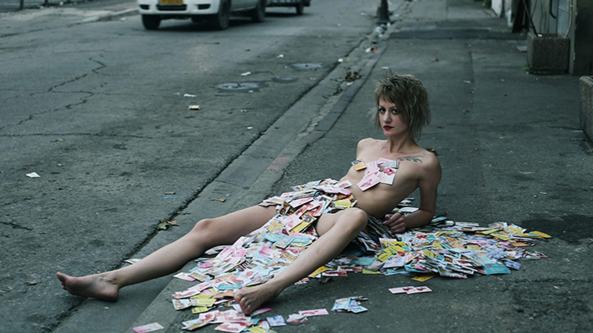 האמנית סשה קורבטוב מכוסה בכרטיסי ביקור של זנות    צילום: וננה בוריאן