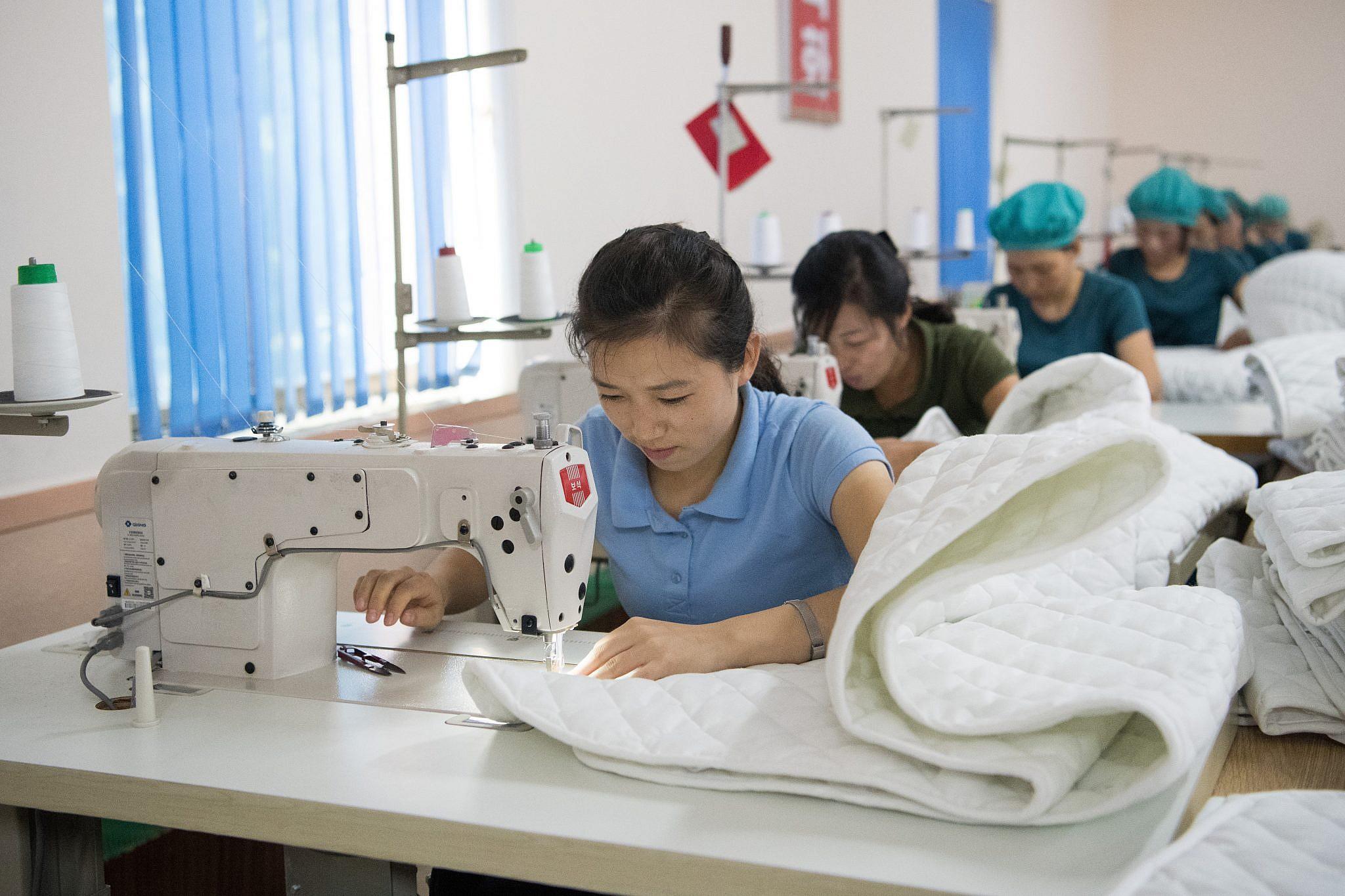 נשים תופרות במפעל בצפון קוריאה | צילום: Carl Court/Getty Images
