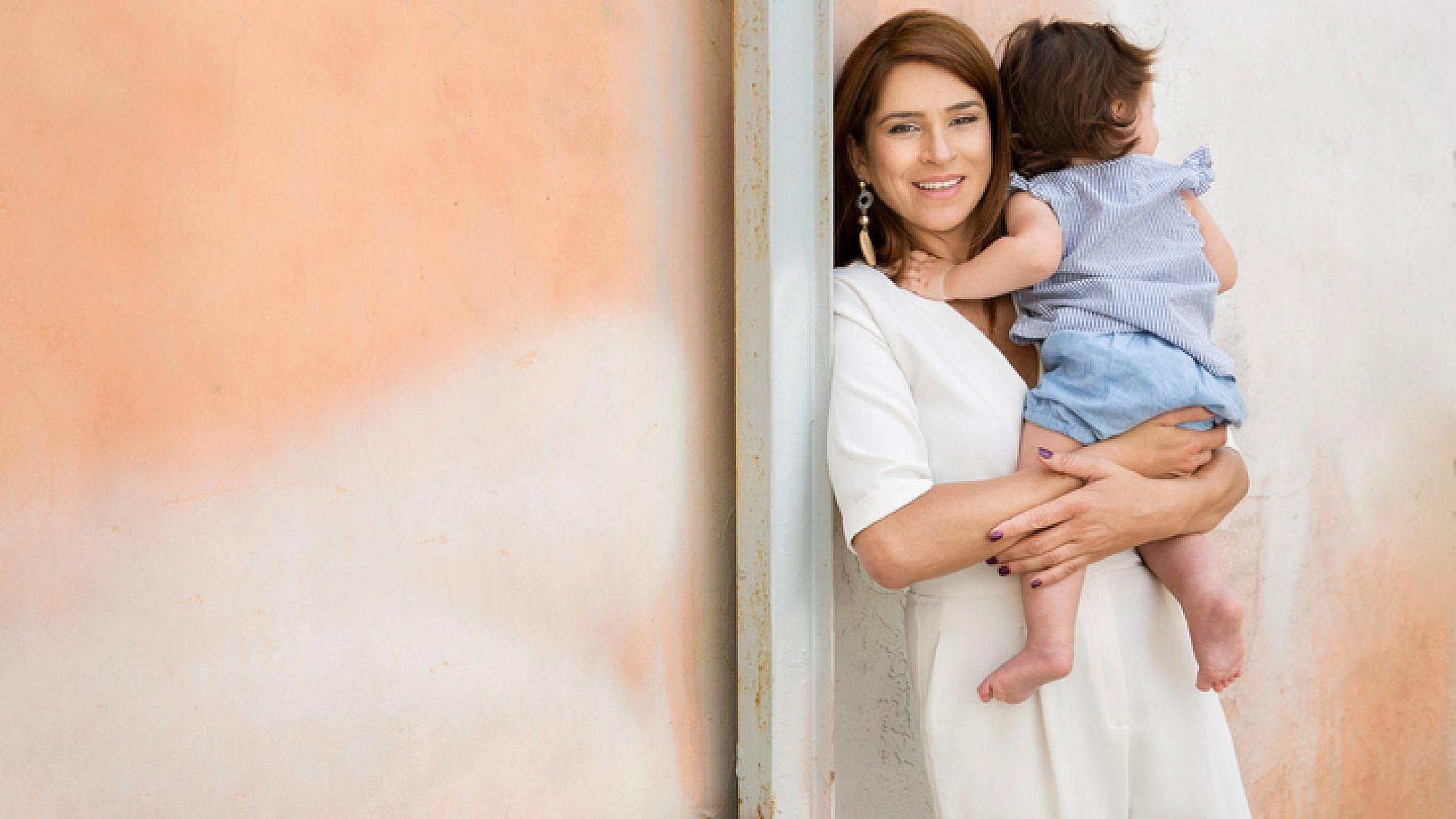 מירב בן ארי באוברול של מנגו, עגילים מסטרדיווריוס. אריאל התינוקת במכנסיים וחולצה מזארה | צילום: ענבל מרמרי, סטיילינג: ליאת גרין