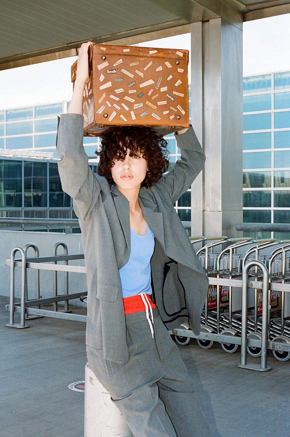 צילום: תום מרשק, סטיילינג: אלין זידקוב לArtbook, דוגמנית: אריאל הלוי לרוברטו. חליפה וחולצה אמריקן וינטג', מכנסיים ומזוודה איתי גונן וינטג'