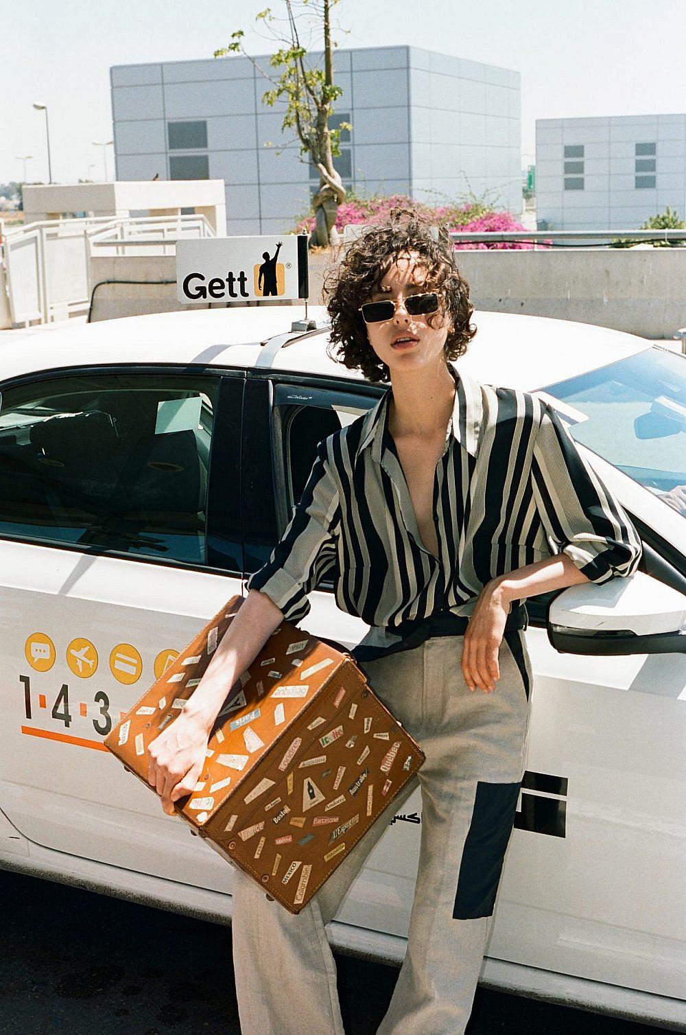 צילום: תום מרשק, סטיילינג: אלין זידקוב לArtbook, דוגמנית: אריאל הלוי לרוברטו. מכנסיים: Ganni בבוטיק ורנר, משקפיים Vogue, חולצה ומזוודה איתי גונן וינטג'