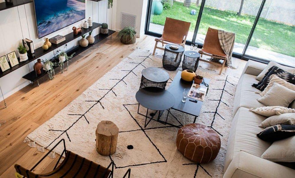 הסלון עוצב בצורה מזמינה לשיחה, עם ספת רביצה גדולה וכורסאות עור ובד משני הצדדים | עיצוב ותכנון: אודליה ברזילי, צילום: גלעד רדט