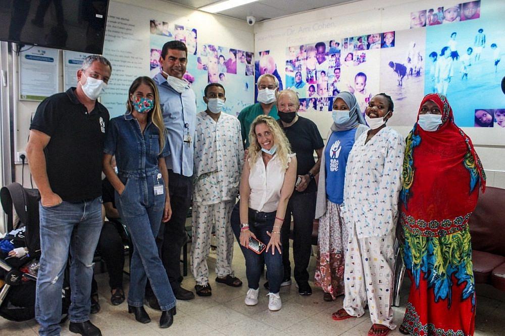 """צוות הרופאים, הנהלת העמותה ומוריס קאהן עם לולסגד בן ה-33 מאתיופיה ואסתר שחזרו לטיפול שני בישראל. בית החולים לילדים ע""""ש סילבן אדמס   צילום: הצל ליבו של ילד"""
