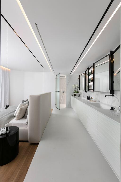 גב המיטה ומאחוריה ארון האמבטיה, כשהמסך המפריד בינהם מורם   עיצוב פנים: אורון מילשטיין, צילום: אלעד גונן