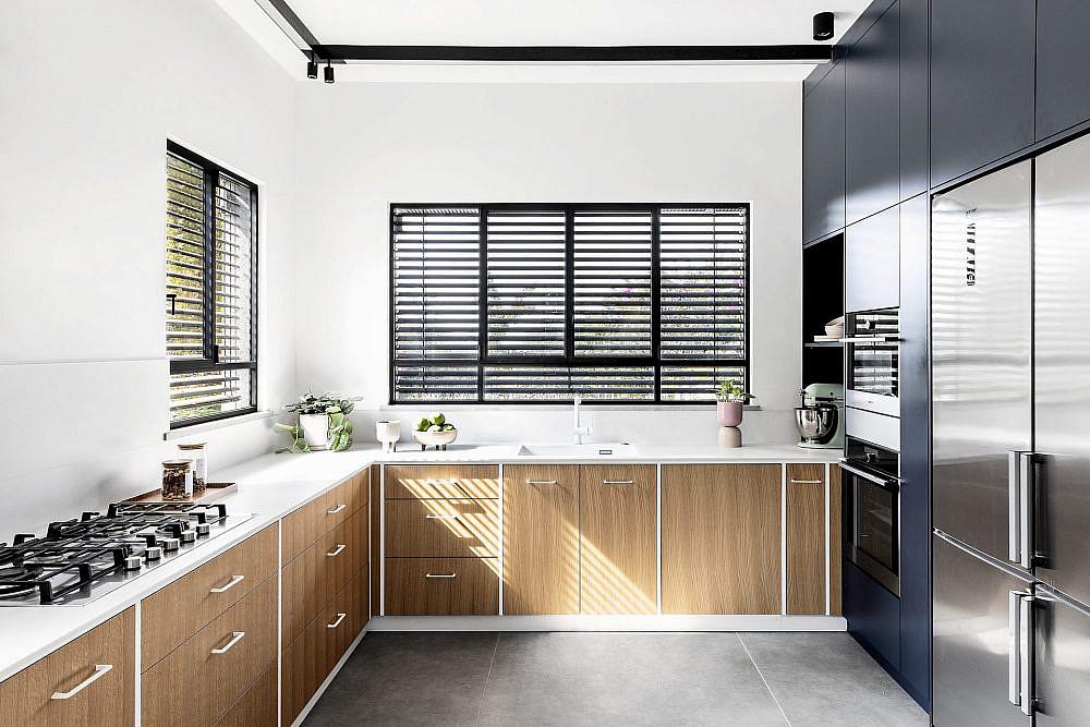 המטבח משלב קיר ארונות בגוון כחול כהה לצד ארונות נמוכים עם דלתות פורניר אלון בחיתוך שטרייפ | צילום: איתי בנית