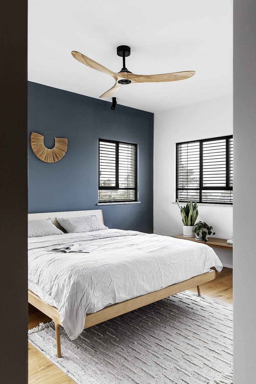 יחידת ההורים שומרת על מראה נקי, כאשר קיר המיטה בלבד נצבע בכחול עמוק ליצירת עניין | צילום: איתי בנית