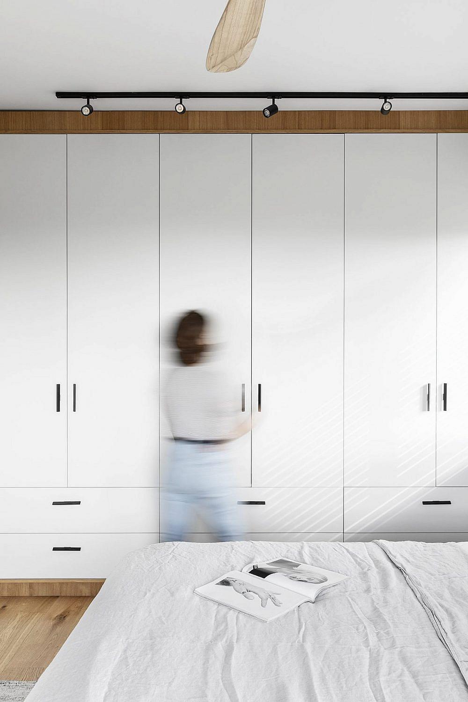 ארון הבגדים בחדר השינה משלים את מראה דלתות החדרים עם בסיס לבן ומסגרת עץ | צילום: איתי בנית