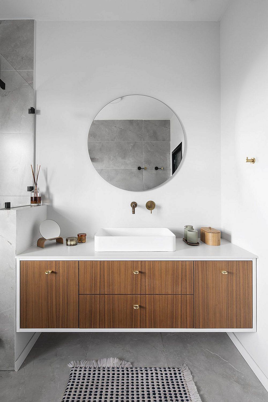 שידת הכיור בחדר הרחצה תואמת לעיצוב ארונות המטבח עם מסגרת לבנה ודלתות פורניר | צילום: איתי בנית